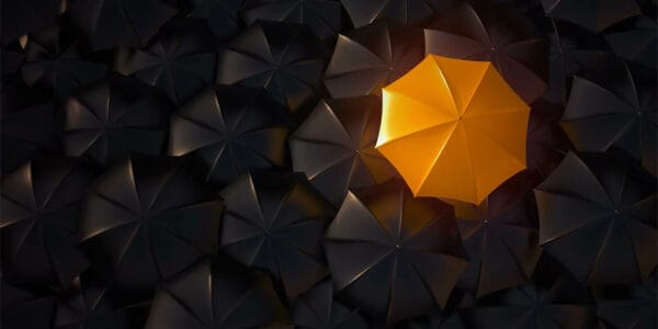 An orange umbrella standing out in a sea of other umbrellas